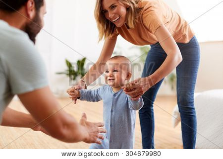 Parents At Home Encouraging Baby Son To Take First Steps