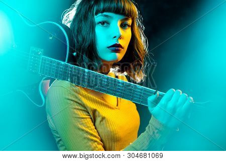 Beautiful Young Hipster Woman With Curly Hair With Red Guitar In Neon Lights. Rock Musician Is Playi