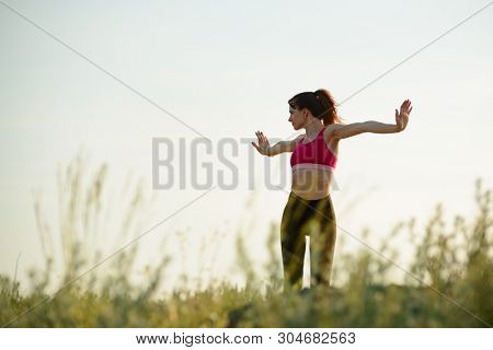 Young Woman Doing Stretching Outdoor. Warm up Exercise in the Hot Summer Evening. Sport and Healthy Active Lifesyle Concept.