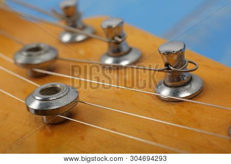 Musical Instrument - Fragment Headstock Peghead Neck Tuning Peg Electric Guitar On A Blue Wood Backg
