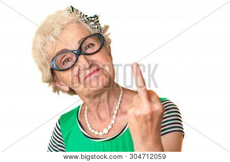 An Older Woman With An Angry Facial Expression Shows Fuck You. Isolated The Concept Of Discontent An