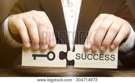 Businessman Collects Wooden Puzzles Key To Success. Concept Of Achieving The Goal, Overcoming Diffic