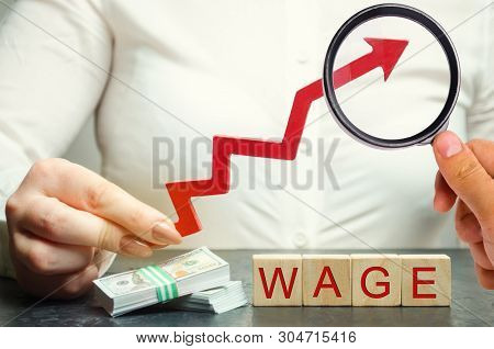 Female Hand Holds Arrow Up Above Word Wage. Increase Of Salary, Wage Rates. Promotion, Career Growth