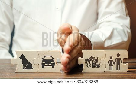A Man Shares Wooden Puzzles With Images Of Property, Children And Pets. The Concept Of Divorce. The