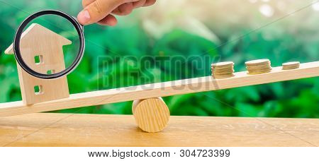 Wooden House With Coins On The Scales. The Concept Of Real Estate Purchase. Sale Of Property. Paymen