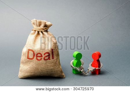 Two People Are Handcuffed To Each Other And Stand Next To The Bag Labeled Deal. Unclosed Obligations