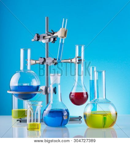 Biological Laboratory. A Tripod With A Variety Of Chemical Glass And Colored Liquids On A Blue Backg
