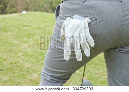Behind The Golfer Standing On The Turfwith White Gloves