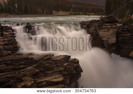 The Mighty Athabasca Waterfall In Banff National Park, Canada, The Torrent Of Water Squeezes Through