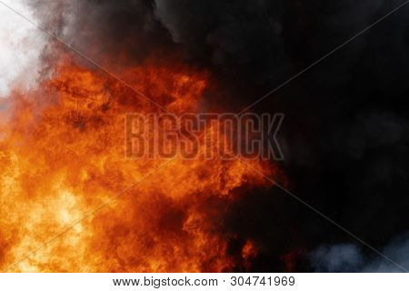 Dangerous Flames Of Red-orange Fire, Motion Clouds Of Black Smoke Covered Sky. Defocus, Motion Blur,