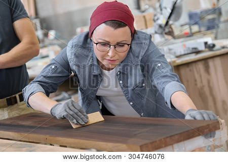 Mature craftswoman working in woodshop. Female painting wooden board with oil, varnish. Furniture joinery wood business. poster