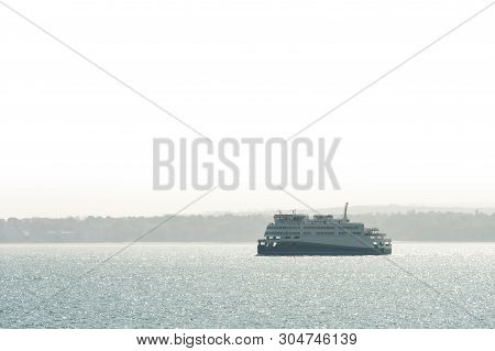 Passenger Ferry On Journey From A Hazy Coastline