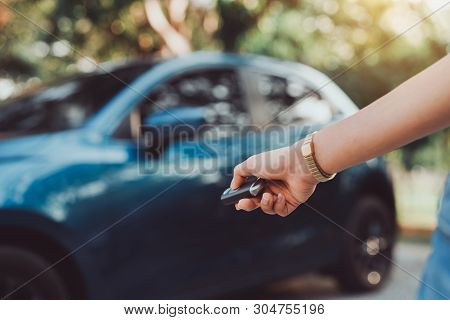 Close Up Hands Woman Pressing Remote Systems Key Near Car For Lock,unlock Of Blue Hatchback Car Near