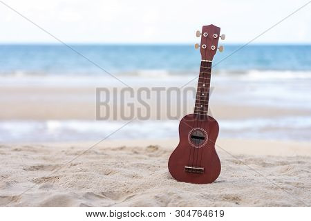 Guitar Ukulele Put On The Sand Beach. Sea View During Daytime With Blue Sky Background. Summer Seaso