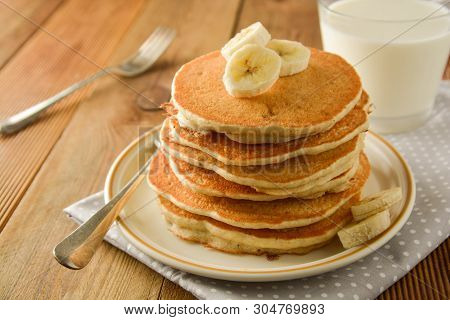 Stack Of Pancakes With Banana Slices And Honey, On Wooden Background. Homemade American Pancakes.