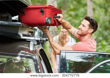 Man packs suitcases in the roof box on the car before traveling on vacation