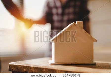 Wooden House Model On Workplace Desk With Construction Worker Team Hands Shaking Greeting Start Up P