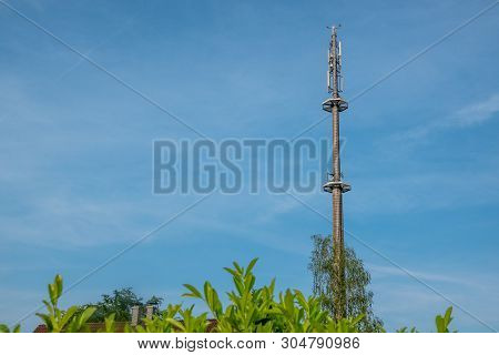 A Radio Mast For The Mobile Phone Network Towers Above A Residential Building Into The Blue Sky In A