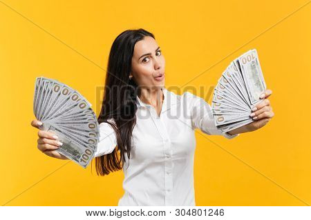 Portrait Of Amazed Young Woman In White Casual Shirt Holding Fan Of Cash Money In Dollar Banknotes I