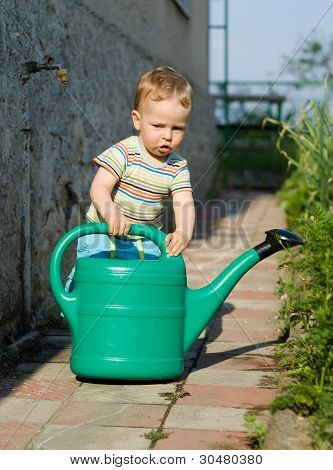 Young Boy Playing With The Watering Can