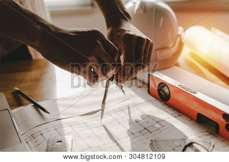 Professional Architect, Engineer Or Interior Hands Drawing With Divider Compass And Blueprint On Wor