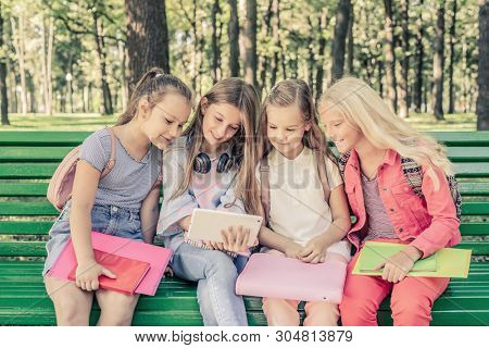Pretty smilng little girls holding notebooks and looking the tablet together sitting on the green bench in the park