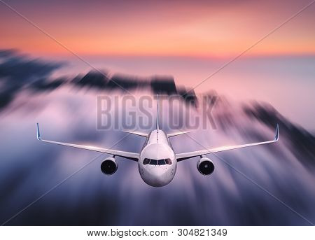 Airplane With Motion Blur Effect Is Flying Over Low Clouds At Sunset. Passenger Airplane, Blurred Cl