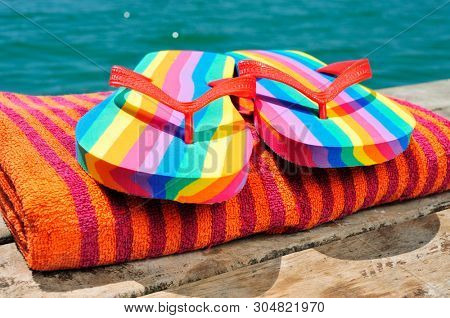 closeup of a pair of rainbow-patterned flip-flops on a orange beach towel, on a weathered dock, next to the ocean or a pond