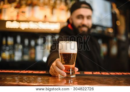 Bearded And Smiling Barman Gives Beer. Cool And Courageous Bar. A Happy Barman Holds A Beer In His H