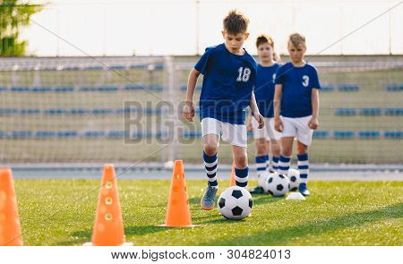 Soccer Camp For Kids. Boys Practice Dribbling In A Field. Players Develop Good Soccer Dribbling Skil