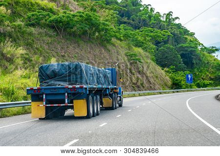 Loaded 22 Wheeler Cargo Semi Trailer Truck Covered And Tied/strapped Down With Rope Driving On Left