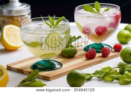 Mojito And Raspberry Mojito Rum Cocktail Drinks With Ingredients, Limes, Lemons, Mint, Brown Sugar A