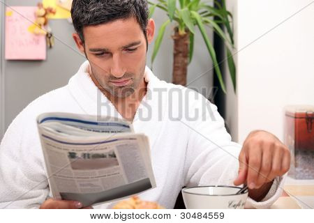 Man having a leisurely breakfast while reading the paper