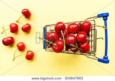 Mini Shopping Grocery Cart Full Of Fresh Cherries. Fresh Berries On Yellow Background. Healthy, Summ
