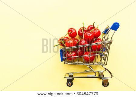Mini Shopping Grocery Cart Full Of Fresh Cherries Fresh Berries On Yellow Background. Healthy Summer