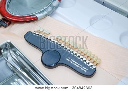 Dentist Checking And Selecting Color Of Young Mans Teeth, Closeup. Teeth Color Chart. Plastic Dental