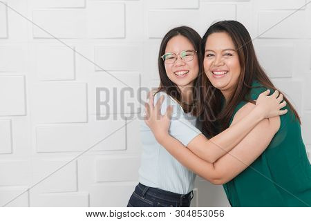 Portrait Of Two Asian Ladies Friends Greeting, Hugging, Embracing Each Other, Very Happy To Be Reuni