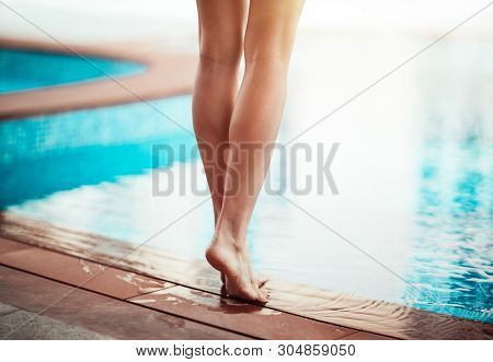 Summer vacation concept, photo of a women's legs, female standing near the pool, barefoot lady with perfect pedicure and smooth skin enjoying weather