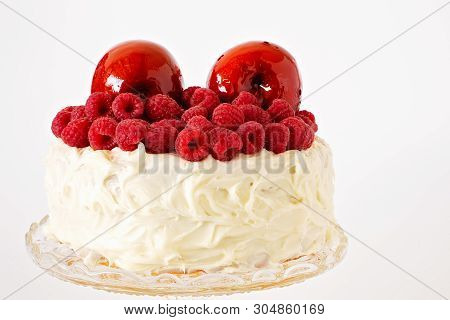 Red Toffee Apples And Raspberries On Top Of A Creamy Frosted Cake On A Glass Plate Isolated On A Whi