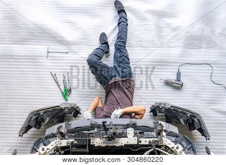 Auto Mechanic Is Assembling Car Parts, Mechanic Changing Car Headlight In A Workshop ,white Backgrou