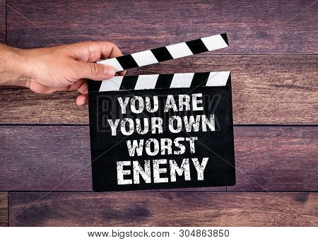 You Are Your Own Worst Enemy. Hand Holding Movie Clapper