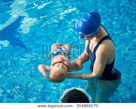 Little Baby Bathing During Health Procedures With Instructor. Trainer In Swimsuit And Swimming Cap H