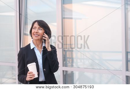 Mature Businesswoman Having A Break In Front Of An Office Building, Talking On The Phone And Drinkin