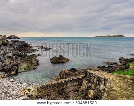 Coast of the Vizcaya village of Mundaca on a beautiful cloudy day, Spain poster