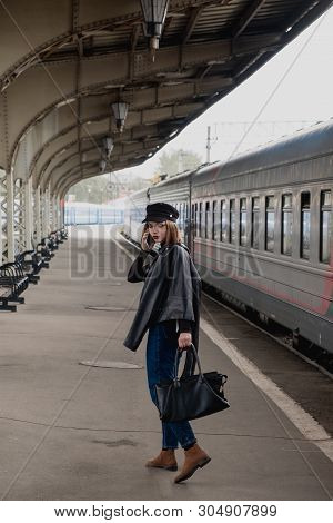 Attractive young woman millenial in black clothes and a hat at the railway station next to the train. Speaks on a mobile phone, smiles and waits for the train. poster