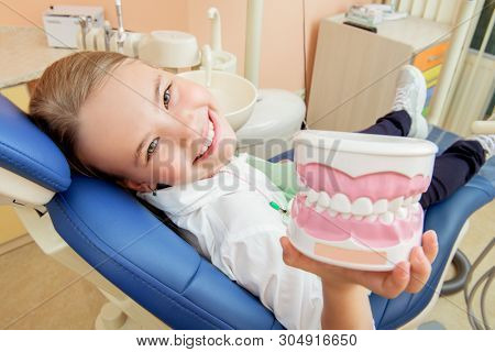 A portrait of a child girl in the cabinet of a dentist. Treatmeat, medicine, hospital.