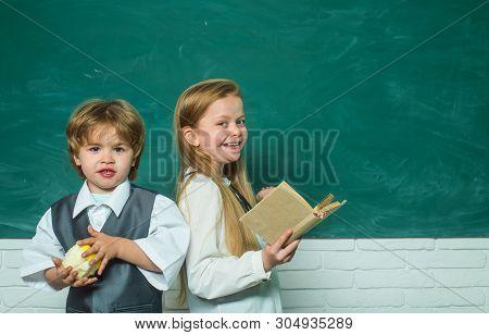 Teacher Schoolgirl Helping Schoolboy With Lesson. Elementary School Kids In Classroom At School. Edu