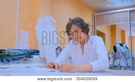 Professional Woman Tailor, Designer Working With Pattern Of New Couture Collection At Atelier, Studi