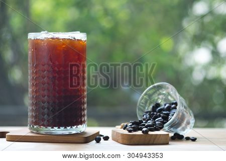 Cold Brewed Iced Coffee In Tall Glass With Coffee Beans With Nature Background