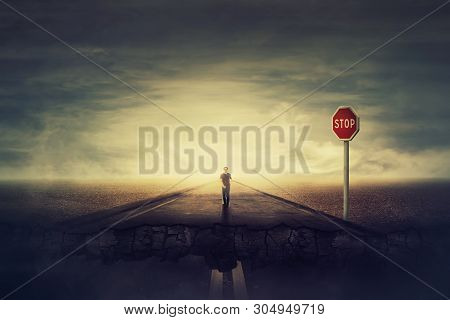 Surreal View As Man Walks A Crushing Asphalt Road As Stop Red Sign Warns Of Danger. Deep Hole In The